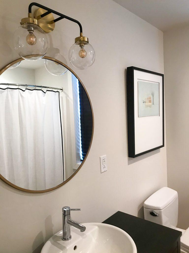 Globe scone above bathroom mirror
